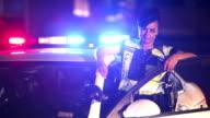 Policewoman standing next to police car, lights flashing