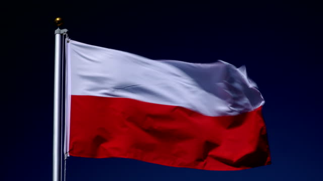 4K: Polish Flag on Flagpole in front of Blue Sky outdoors (Poland)