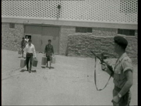 Al Mansoura GV Detention Centre Zoom into armoured door MS 2 soldiers with guns at ready Pan sandbags BV Armoured Car through gate MS Soldier with...