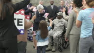 A politician greeting a soldier sitting in a wheelchair