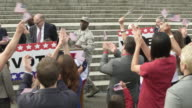 A politician introducing a soldier to an applauding crowd