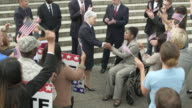 A politician shaking hands with a disabled woman
