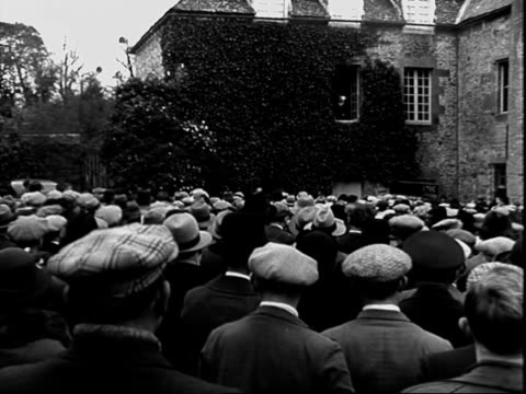 Politician speaking into microphone at rally in rural France men seated in row while listening to speech / Men reading posted news bulletins and...