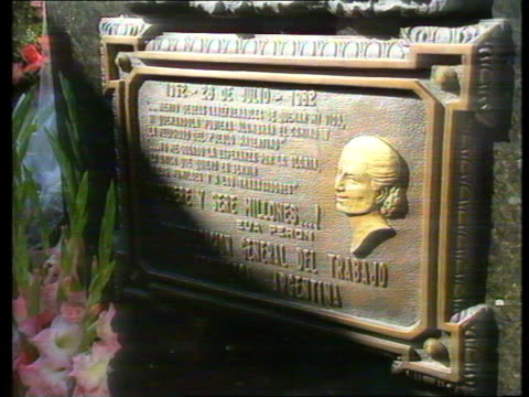 Carlos Menem Wins Elections EXT/DAY Tomb of Eva Peron MS Peronists bedecking tomb with flags as flowers dominateTCMS Bronze basrelief depicting...