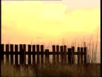 NorthSouth Divide A Tale of Two Brothers SIDE Mongan family entering stadium Seaham MS Wooden fence silhouetted against pale orange sky Overgrown...