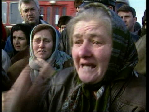 Russia Tightening Grip on Chechnya ITN GV Refugees gathered round bus CS Refugee woman seen through window of bus MS Refugees standing at door of bus...
