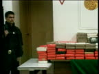 Elections Fuentes death ITN MEXICO Mexico City Police officer guarding drugs haul ZOOM IN packets of drugs stacked on table PAN LR