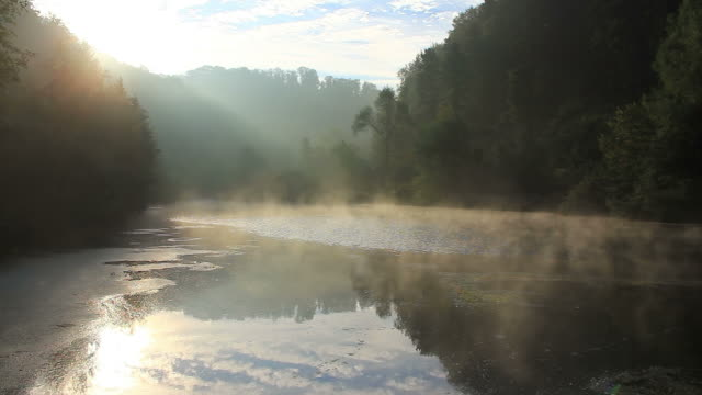 Pond in early fall, water steaming in morning sun