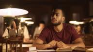 DS Pondering afroamerikanische männliche Sitzbereich in der Bibliothek