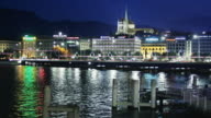 T/L WS Pont du Mont-Blanc crossing Rhone river with St Pierre Cathedral illuminated at night, Geneva, Switzerland
