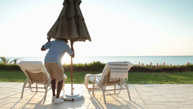 WS Pool attendant at hotel walks in to shot, puts up parasol then walks away.