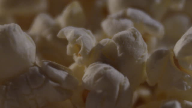 ECU of popcorn with a stream of butter landing on popcorn.
