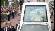 day three ENGLAND London Pope waving as towards in popemobile past crowd of people lining street