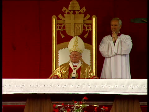 Pope John Paul II wearing mitre leading religious service from throne Poland
