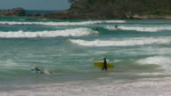 Port Macquarie Town Beach surf beach 2 anonymous boys with surfboards walk into surf one jumps on and start paddling out / wide shot and pan surf and...