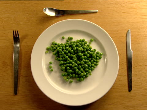 Portion of peas on white plate surrounded by modern cutlery