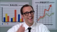 CU Portrait businessman with glasses smiling and giving thumbs up and OK sign in front of graphs/ New York City