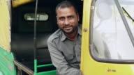 Portrait of a auto rickshaw driver smiling, Delhi, India
