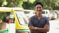 Portrait of a auto rickshaw driver smiling, Delhi, India