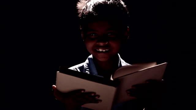 Portrait of a boy reading a book