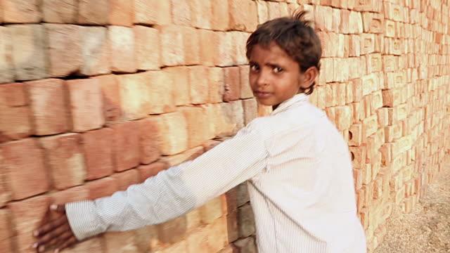 Portrait of a boy walking at brick factory, Haryana, India