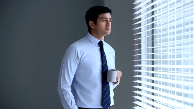 Portrait of a businessman drinking tea, Delhi, India