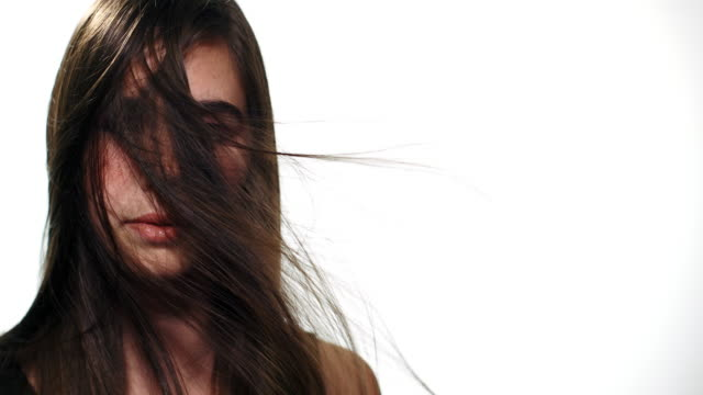 Portrait of a caucasian girl looking into camera while her hair blows across her face.