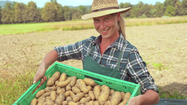 Portrait of a female farmer taking potatoes out of the delivery truck