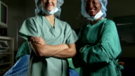 Portrait of a female surgeon and nurse in scrubs with arms crossed smiling