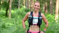 SLO MO Portrait of a female trail running competitor in the forest