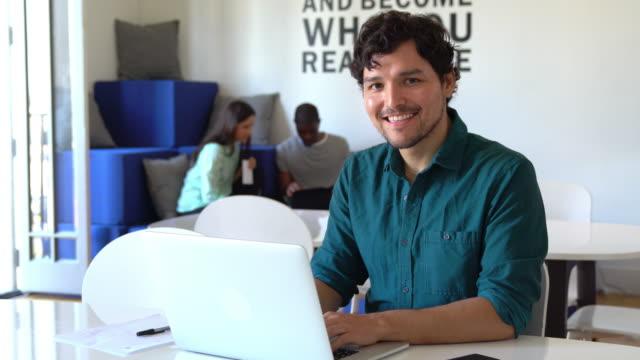 Portrait of a man using a laptop in a modern office
