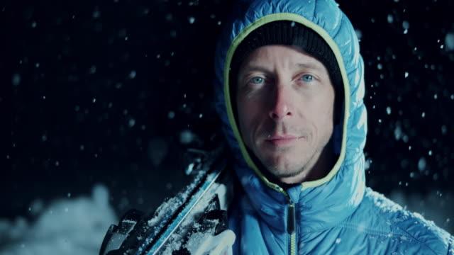 SLO MO porträtt av en man med skidor i snöfall
