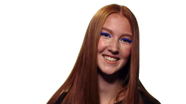 Portrait of a redheaded teen looking into camera smiling.