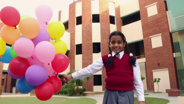 Portrait of a schoolgirl holding balloons, Noida, Uttar Pradesh, India