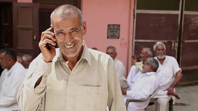 Portrait of a senior man talking on a mobile phone, Haryana, India