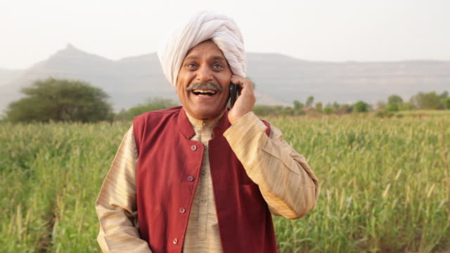 Portrait of a senior man talking on a mobile phone in a farm