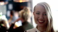 Portrait of a smiling blonde woman in bar