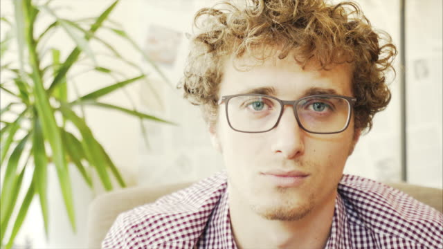Porträt eines lächelnden jungen Mannes in einem Café.