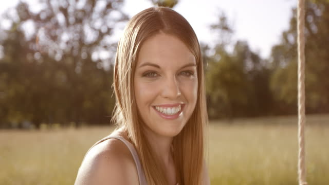 SLO MO portret van een lachende jonge vrouw die zit op een schommel