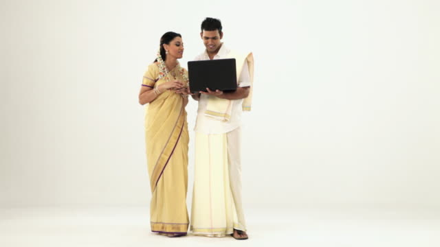 Portrait of a south Indian couple shopping from a laptop through credit card