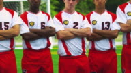 A group of soccer players stand together with their arms crossed.