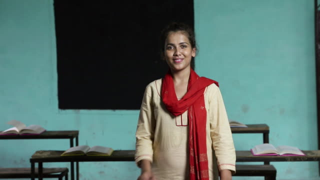 Portrait of a university student smiling in the classroom, Haryana, India
