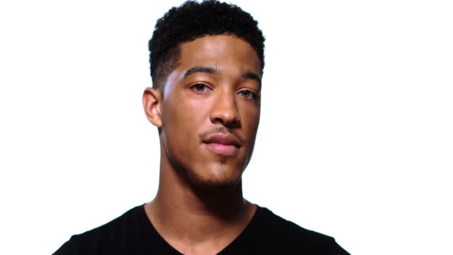 A portrait of a young black man turning towards camera with a blank expression.