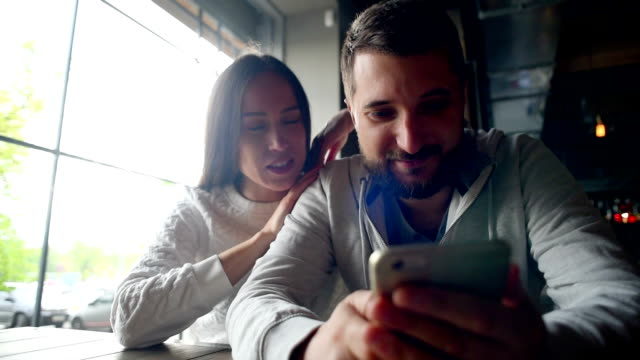 Portrait of a young couple with smartphone sitting in a restaurant