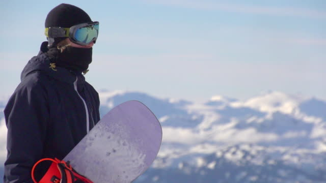 Portrait of a young man standing with his snowboard on a scenic snow covered mountain top.  - Super Slow Motion - filmed at 240 fps