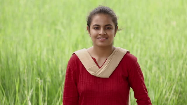 Portrait of a young woman showing medal in the farm, Haryana, India