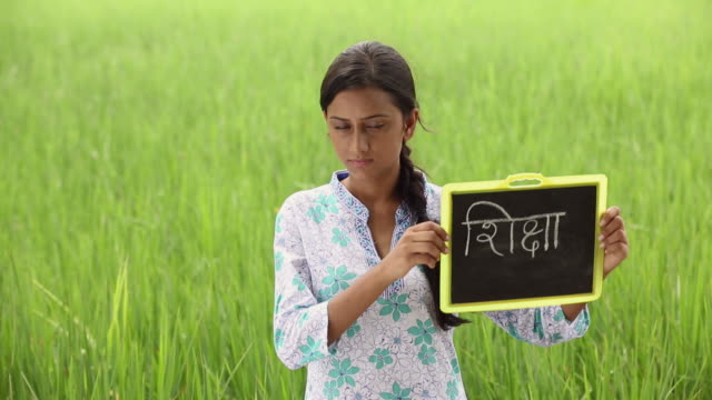 Portrait of a young woman showing slate in the farm, Haryana, India