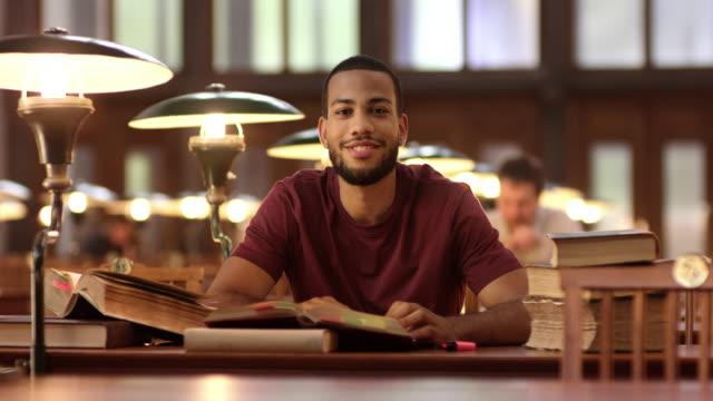 DS portret van een Afro-Amerikaanse man studeren in de bibliotheek