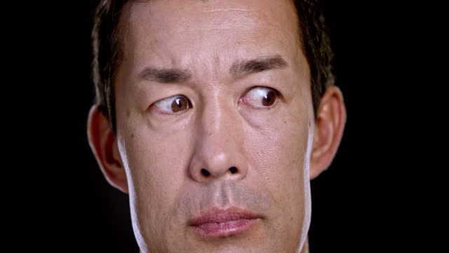 Portrait of an Asian male moving eyes around while facing forward