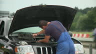 MS Portrait of auto mechanic repairing broken down car next to highway, Ljubljana, Slovenia